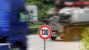 Laster rasen auf einer Autobahn an einem Tempo 130 Schild vorbei