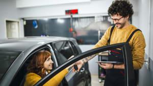 Frau im Auto übergibt Automechaniker den Autoschlüssel