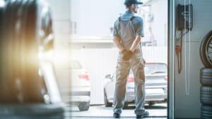 Automechaniker hält Ausschau nach Lieferanten der Ersatzteile um Auto fertig reparieren zu können