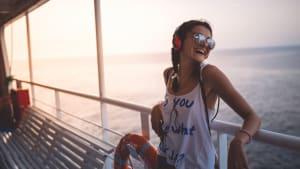 Eine Frau lehnt lachend an der Reling eines Schiffes.