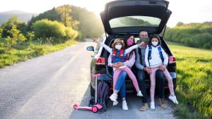 Familie mit Corona Schutzmasken sitz im Kofferraum Ihres Autos auf einer Straße in Frühlingslandschaft