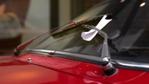 Ein Strafzettel hängt an der Autoscheibe