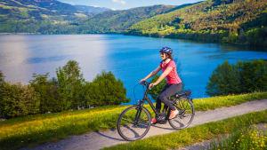 Frau fährt mit ihrem Pedelec an einem See vorbei