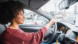 fröhliche Frau am Steuer Ihres Autos