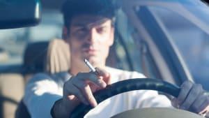 Mann fährt Auto mit Zigarette in der Hand