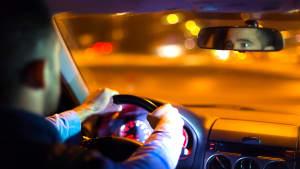 Ein Mann fährt Auto bei Dunkelheit