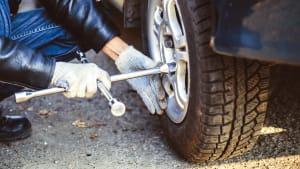 Mann wechselt Reifen