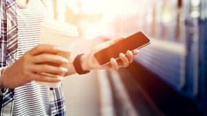 Eine Frau steht mit ihrem Smartphone und einen Coffee-to-go Becher vor einem Zug