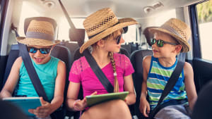 Drei Kinder auf der Rückbank eines Autos