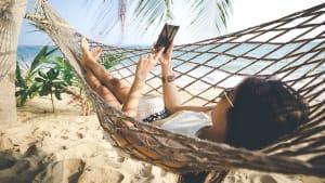 Eine Frau liegt mit ihrem Smartphone in einer Hängematte am Strand