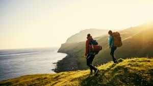 Ein Mann und eine Frau wandern mit Rucksack auf Klippen über dem Meer