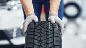 Mechaniker rollt Reifen durch eine Werkstatt