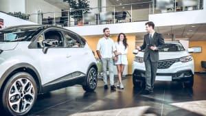 Autohändler berät Paar bei Autokauf