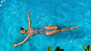 Eine Frau erholt isch im Pool beim schwimmen
