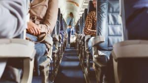 junge Frau im Gang eines Flugzeugs