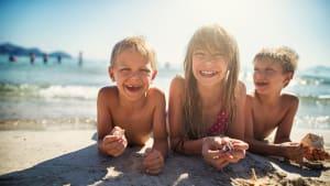 Drei Kinder liegen lachend am Strand im Wasser.