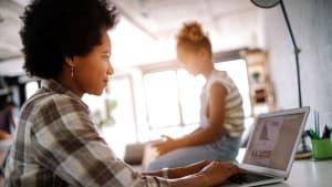 Eine Mutter bucht eine Reise im Internet, das Kind schaut zu