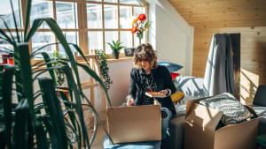 Junge Frau zieht während der Coronakrise in einen neue Wohnung um und packt Kisten aus