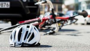 Fahrrad und Fahrradhelm liegen nach einem Unfall auf der Straße