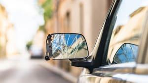 Nahaufnahme eines kaputten Außenspiegels nach einem Unfall