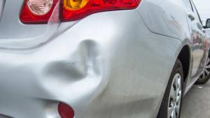 Silbernes Auto mit großer Delle im Kofferraum