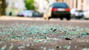 Glassplitter liegen am Boden. Im Hintergrund fährt ein Auto