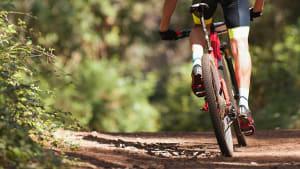 Ein Mountainbiker fährt auf einem unbefestigten Feldweg in hohem Tempo