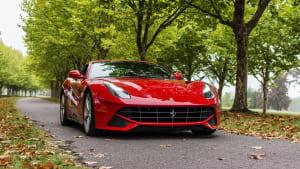 Roter Ferrari auf laendlicher Strasse im Herbst
