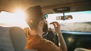 Mann kämmt sich den Bart am Steuer eines Autos bei der Fahrt im Sonnenaufgang