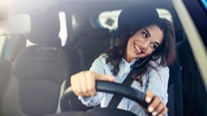 Eine Frau telefoniert während des Autofahrens, sie hat das handy zwischen Schulter und Kopf geklemmt