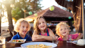 Drei Kinder sitzen im Urlaub am Strand beim Essen