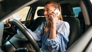 Frau telefoniert beim Autofahren und ist nicht angeschnallt