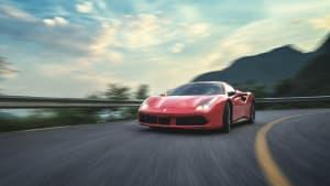 Ein roter Ferrari fährt dynamisch durch eine Kurve