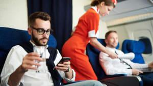 Fluggast arbeitet am Handy auf seinem Sitzplatz in der Businessclass