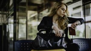 Eine Frau sitzt am Flughafen mit Koffern vor sich stehend und schauf auf die Uhr