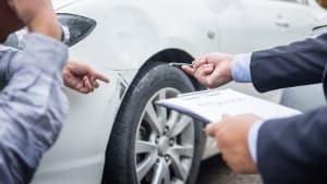 Zwei Männer mit Klemmbrett stehen vor einem Wagen mit einem Unfallschaden.