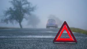 Ein Auto mit einer Panne steht im Halbdunklen unbeleuchtet auf einer Straße, im Vordergrund ist ein Warndreieck zu sehen.
