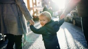 Kleiner Junge geht an der Hand seiner Eltern