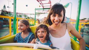 Frau fährt mit Kindern in der Achterbahn