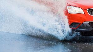 Auto fährt über eine überschwemmte Strasse