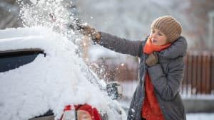 Frau kratzt Schnee und Eis von ihrem Auto