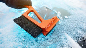 Hand räumt verschneite Autoscheibe mit einem Eiskratzer frei