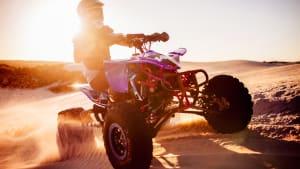 Ein Quadfahrer fährt über eine Sanddüne