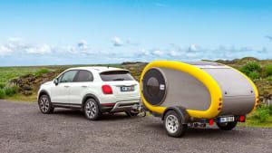 Ein kleiner weisser Fiat mit einem kleinen Caravan-Anhänger
