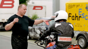 Ein Fahrschullehrer erklärt einem Schüler auf dem Motorrad die Regeln