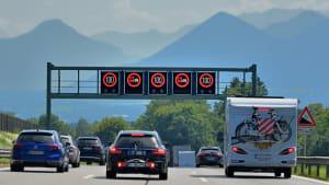 Autos fahren auf einer Autobahn unter einem Geschwindigkeits-Begrenzungsschild