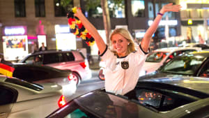 Junge Frau bei einem Fußball Autokorso mit Deutschland Blumenkranz in der Hand