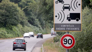 Ein Schild mit dem Hinweis zur automatischen Blitzkontrolle steht an einer Straße in Frankreich