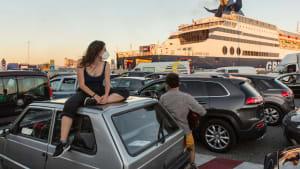 Frau mit Maske sitzt auf einem Autodach am Fährnaleger in Olbia