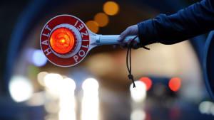 Polizeikontrolle - ausgestreckter Arm mit Polizei Kelle in der Nacht